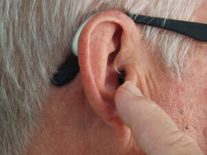 older mans ear being touched by his finger